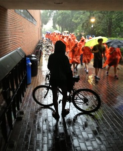 Umbrellas up, a University of Florida tour parades through the rain and past a student at Weimer Hall. Professor John Freeman shot this photo with his iPhone. (Credited to John Freeman, with permission)